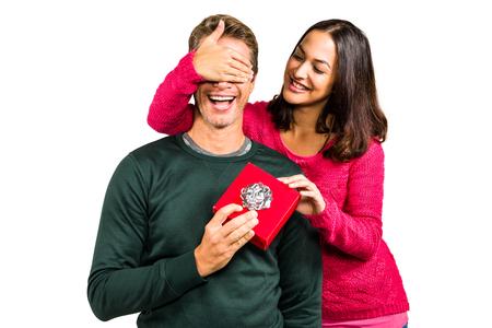 closing eyes: Smiling girlfriend closing eyes of boyfriend against white backkground Stock Photo