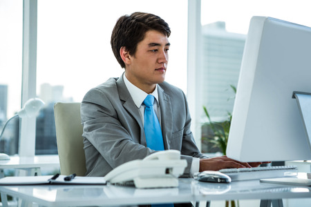 businessman working at his computer: Businessman working on his computer in an office Stock Photo