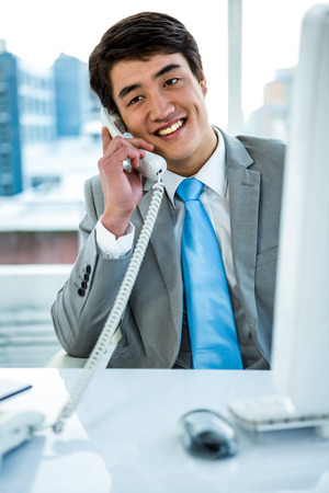 landline phone: Businessman making a phone call in an office