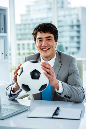 thumps up: Asian businessman holding soccer ball with thumps up in office