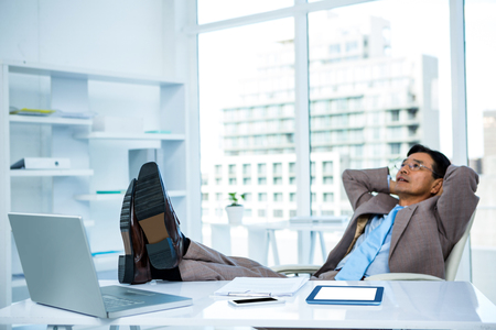 feet on desk: Businessman relaxing with his feet on his desk in office