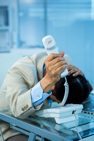 overwhelmed: Overwhelmed asian businessman answering the phone in office Stock Photo