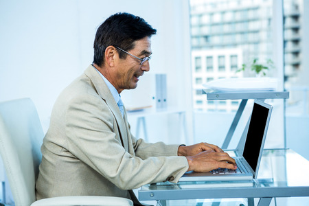 businessman suit: Smiling asian businessman working on laptop in office