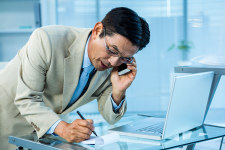 overwhelmed: Overwhelmed asian businessman answering the phone and writing