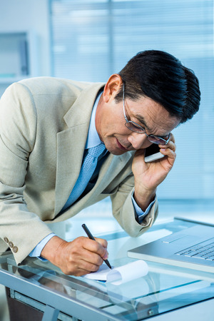 overwhelmed: Overwhelmed asian businessman answering the phone and writing in office
