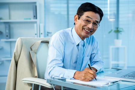 usando computadora: Sonriente hombre de negocios asiático escribir un informe en el cargo