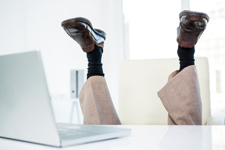 feet up: Businessman lying on the ground with feet up in office