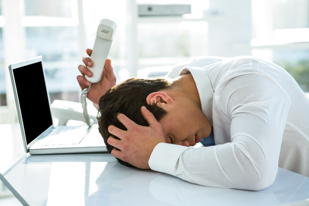 Overwhelmed asian businessman answering the phone in office Stock Photo