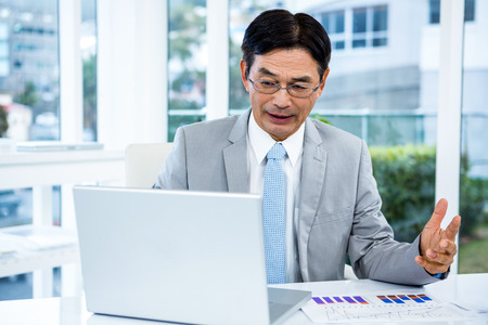 businessman working at his computer: Asian businessman working in his computer in an office