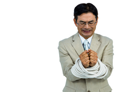 tied up: Asian businessman tied up in rope on white background