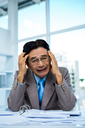 worried businessman: Worried businessman working at his desk in office