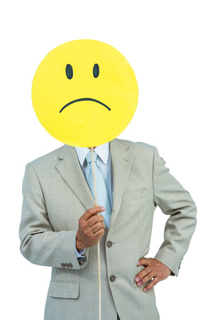 angry smiley face: Businessman holding angry smiley face balloon on white background