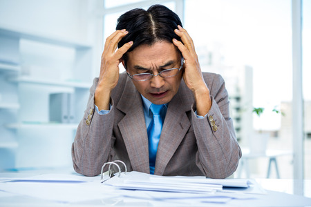 pounding head: Worried businessman working at his desk in office
