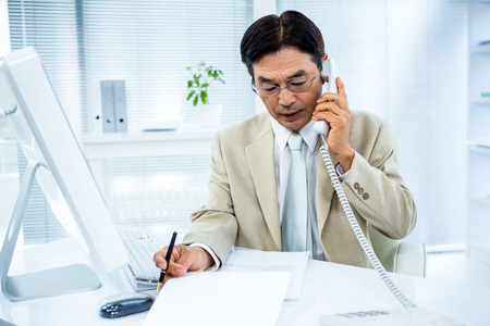 Serious businessman talking on the phone in his desk Stock Photo
