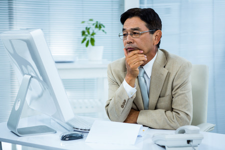 black man: Undecided businessman at his computer in his office