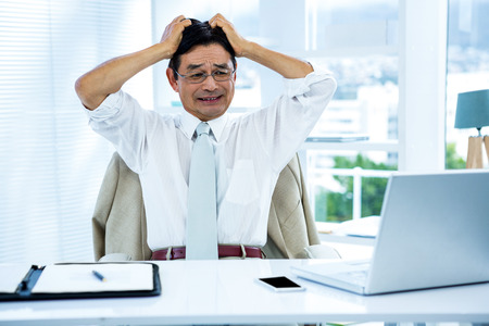 going crazy: Overwhelmed asian businessman going crazy in office