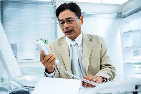 Frustrated businessman looks his phone in his office