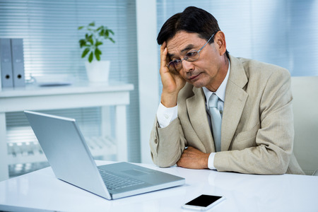 undecided: Undecided businessman looks his computer in his office Stock Photo