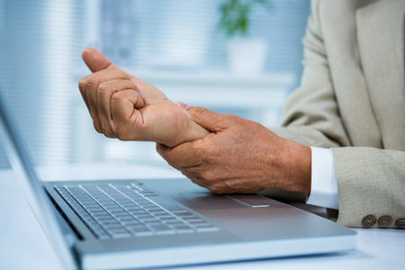 Businessman with wrist pain at his computer Stock Photo