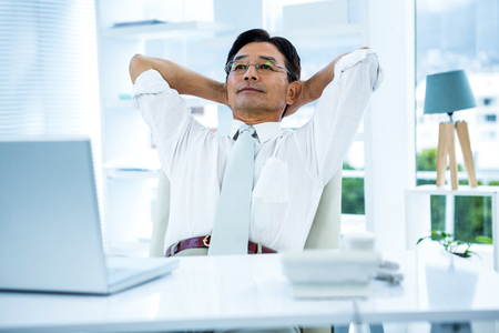 break from work: Smiling asian businessman stretching in office