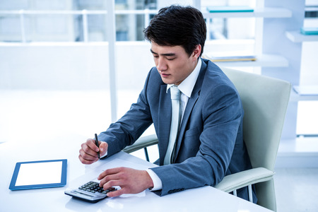 concentrated: Concentrated asian businessman is working in his office Stock Photo