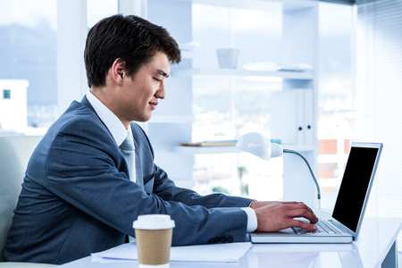 Asian businessman using his computer in his office