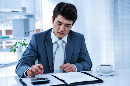 concentrated: Concentrated asian businessman use calculator in his office