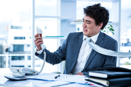 outraged: Angry asian businessman shouting on the phone in his office