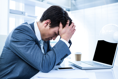 dreariness: Sad businessman holding his head in his office