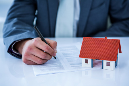 new contract: Businessman signing contract for new house in a office Stock Photo