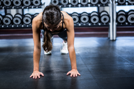 plank position: Fit woman doing push ups exercises at gym Stock Photo