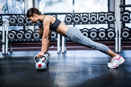 push ups: Fit woman doing push ups with kettlebells at gym