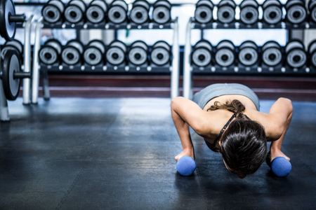 push ups: Fit woman doing push ups with dumbbells at gym