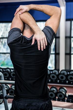 estiramiento: Vista trasera del hombre que estira los brazos en el gimnasio