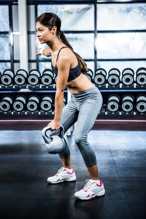weight room: Serious fit woman lifting kettlebell at gym
