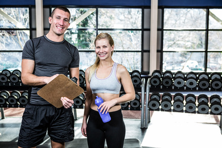 adult  body writing: Fit woman discussing performance with trainer at gym