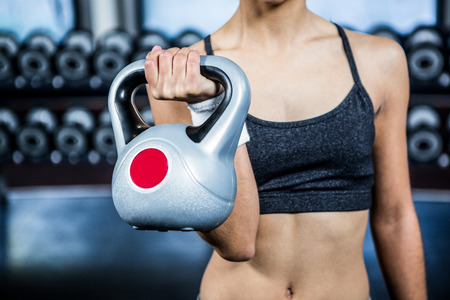 Cropped image of fit woman lifting kettlebell at gym Stock Photo