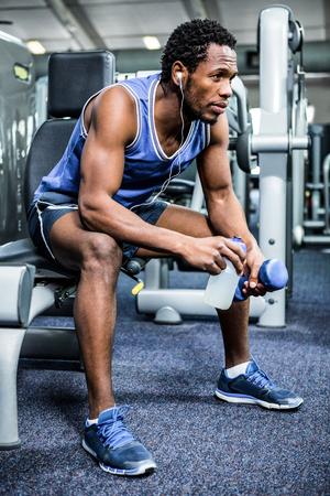 taking a break: Thoughtful muscular man taking a break at gym