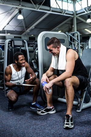 adult  body writing: Muscular man discussing performance with trainer at gym