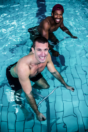 leisure centre: Fit men cycling in the pool at the leisure centre Stock Photo