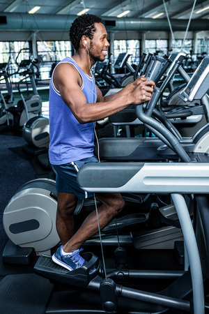 Smiling man working out with headphones on at the gym