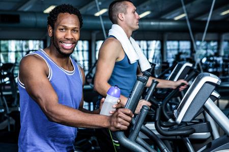 eliptica: Hombre sonriente que usa la m�quina el�ptica en el gimnasio