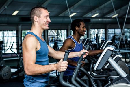eliptica: Sonrientes hombres que usan la máquina elíptica en el gimnasio