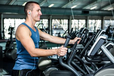 elliptical: Smiling muscular man using elliptical machine at gym Stock Photo
