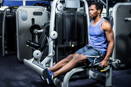 workout gym: Serious muscular man using exercise machine at gym