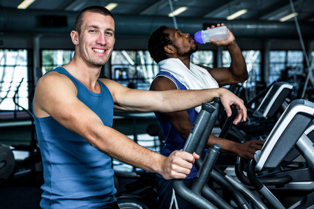 elliptical: Smiling man using elliptical machine at gym