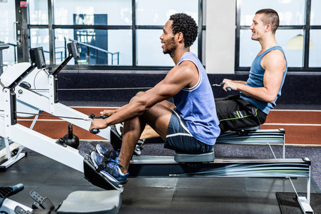 Muscular men using rowing machine at gym Stock Photo