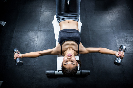 crossfit: Muscular woman lifting dumbbell while sitting on bench in crossfit