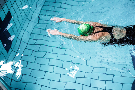 swimming goggles: Fit woman swimming with swimming hat in swimming pool