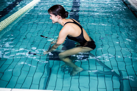 Side view of woman cycling in the pool Stock Photo